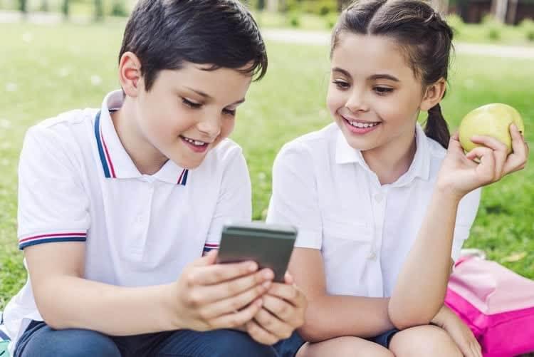 Школьник и школьница смотрят в смартфон