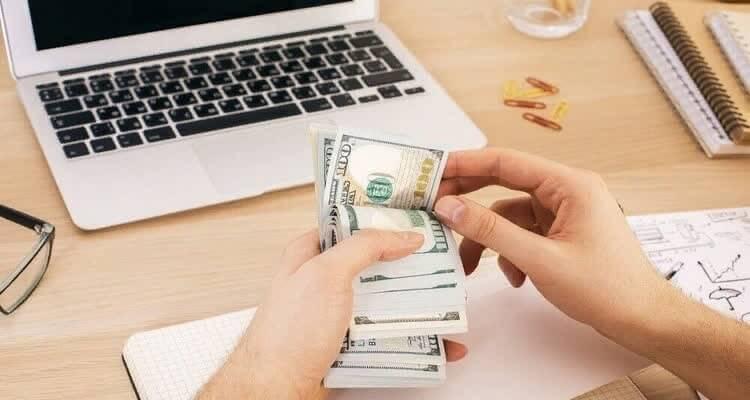 Деньги в руках за выполнение заданий и ноутбук