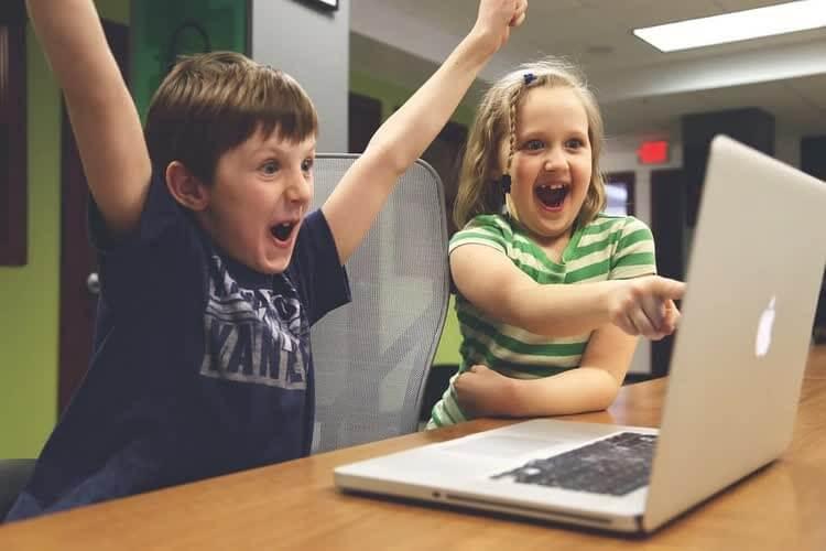 Мальчик и девочка довольны результатом у компьютера