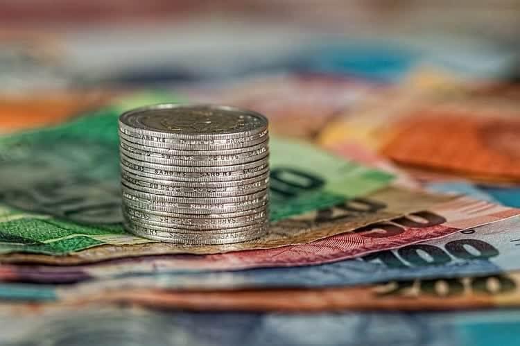 Стопка монет на бумажных купюрах